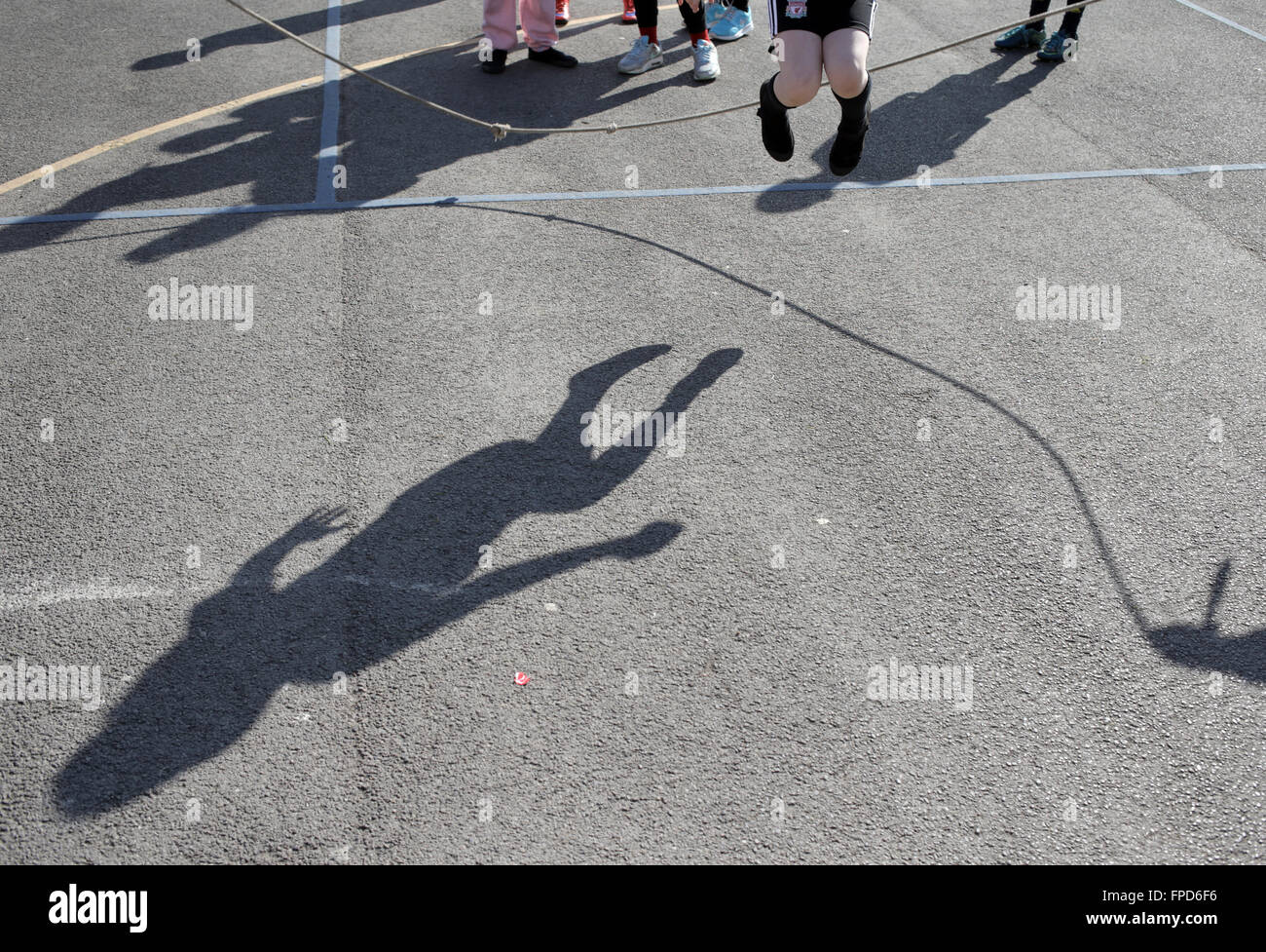 Pupils skipping during playtime at Red Hall Junior School in Darlington, County Durham, UK. - Stock Image