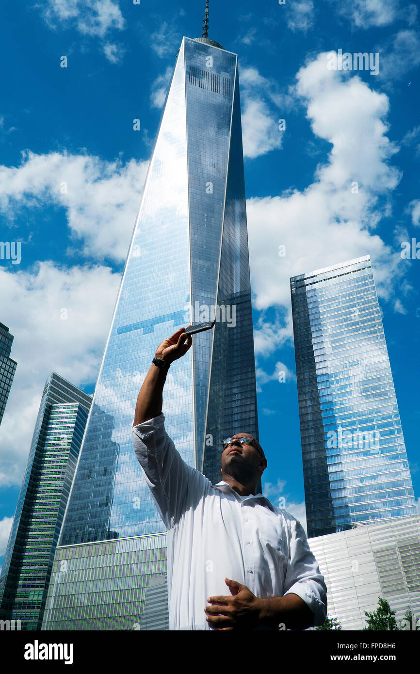 A man takes a 'selfie' with a smartphone in front of the World Trade Building in Manhattan. - Stock Image