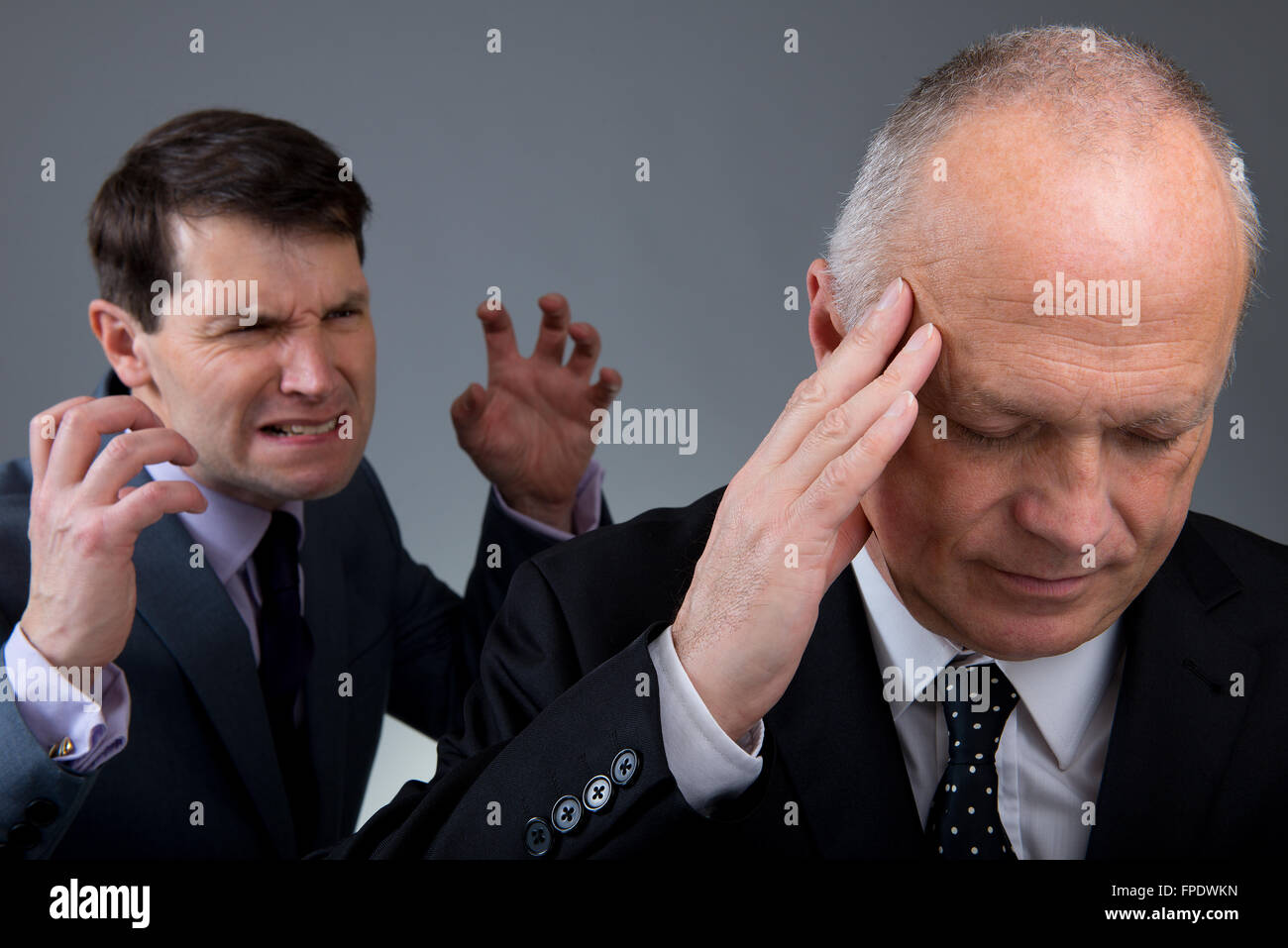 Calm/pensive businessman in the foreground, with angry/frustrated work colleague behind him. - Stock Image