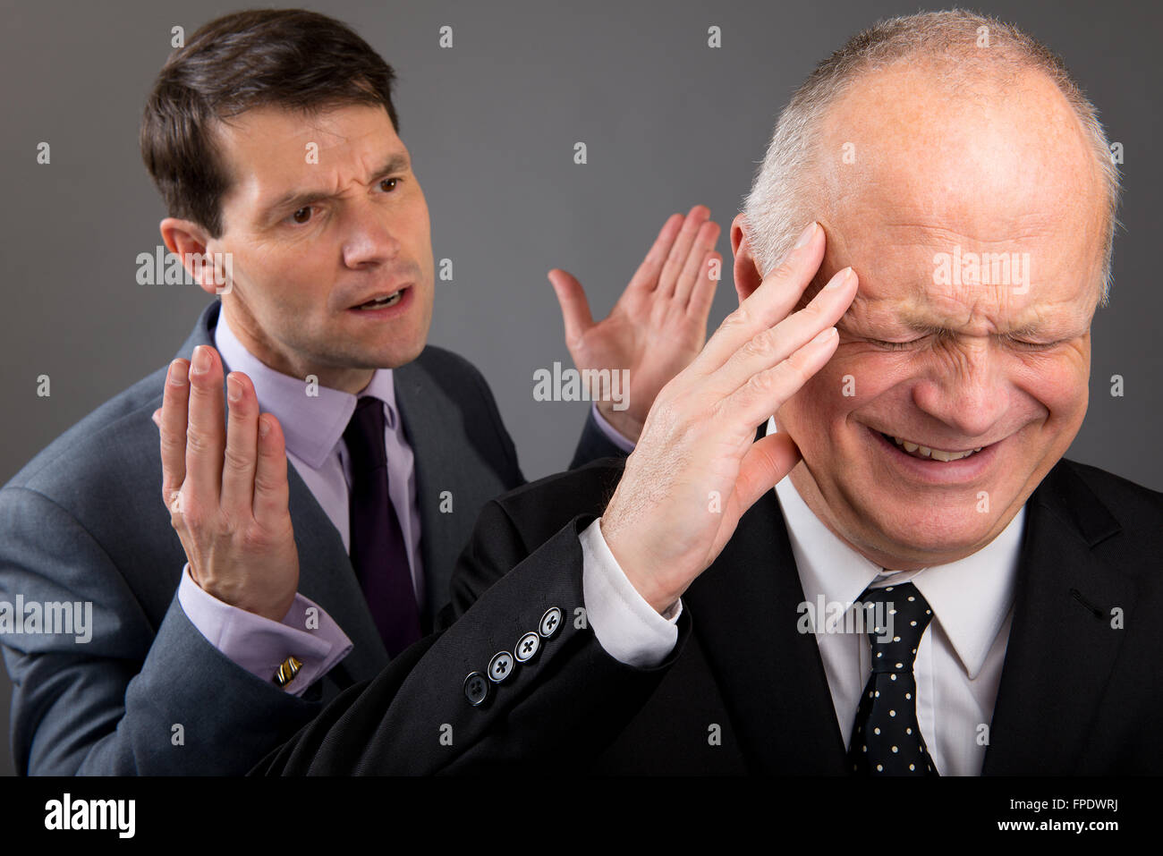 Tearful/stressed businessman in the foreground, with work colleague making open hands gesture behind him. - Stock Image