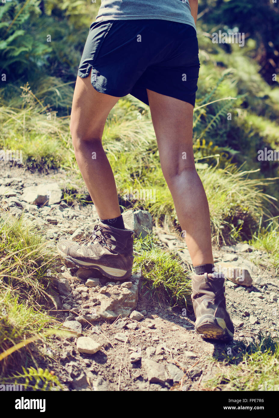 Young woman wearing sturdy hiking boots climbing up a rocky mountain footpath in a health and fitness concept, close - Stock Image