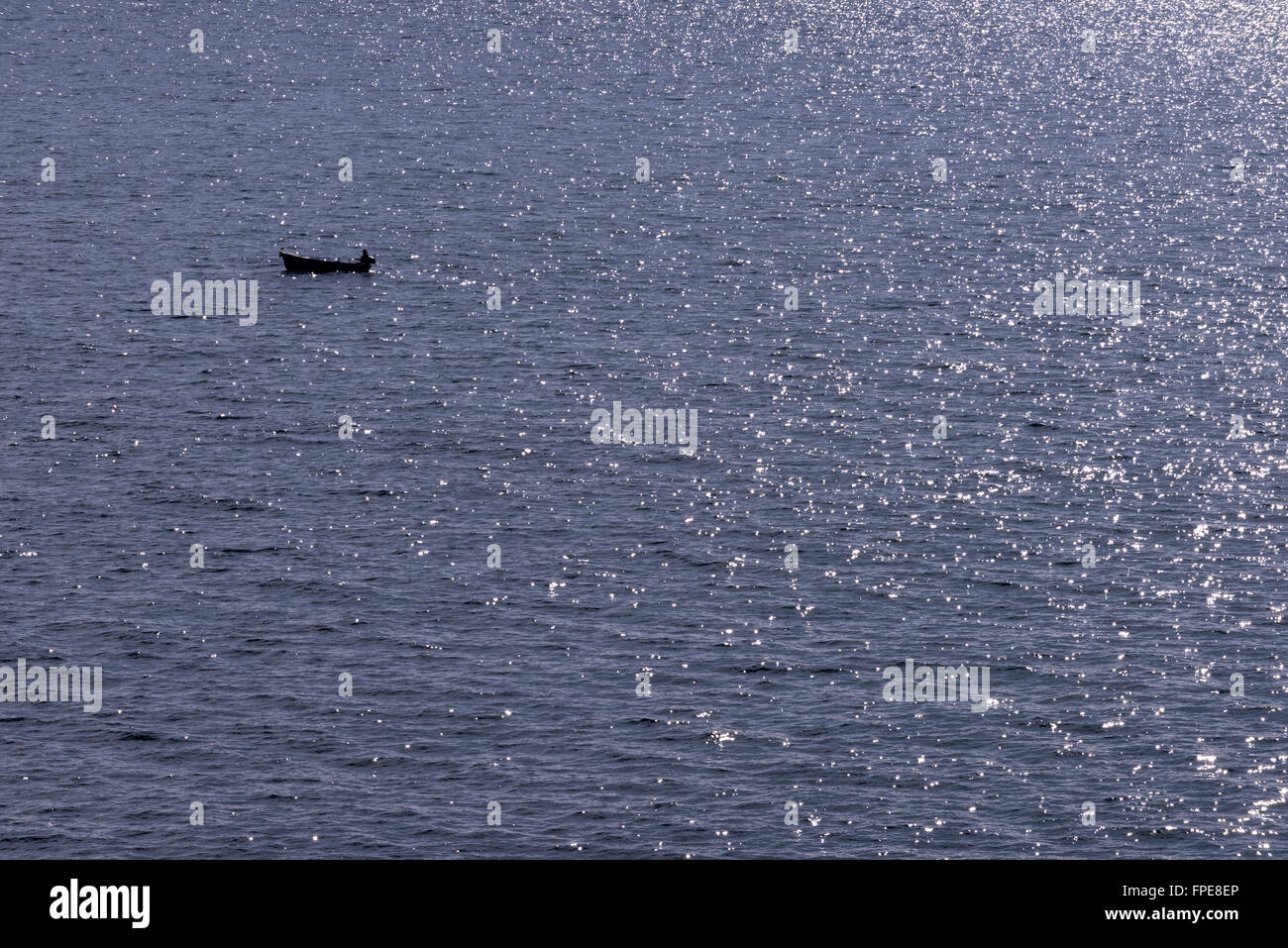 A lone fisherman on a sparkling Adriatic Sea, near Dubrovnik, Croatia. - Stock Image