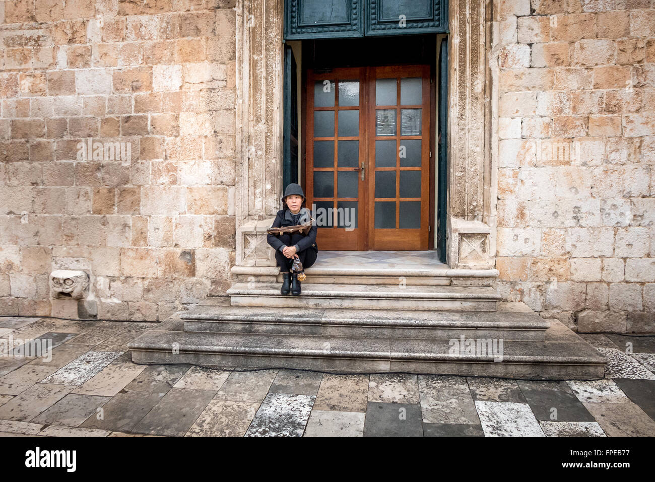 A tourist sitting on steps in the old city of Dubrovnik. - Stock Image