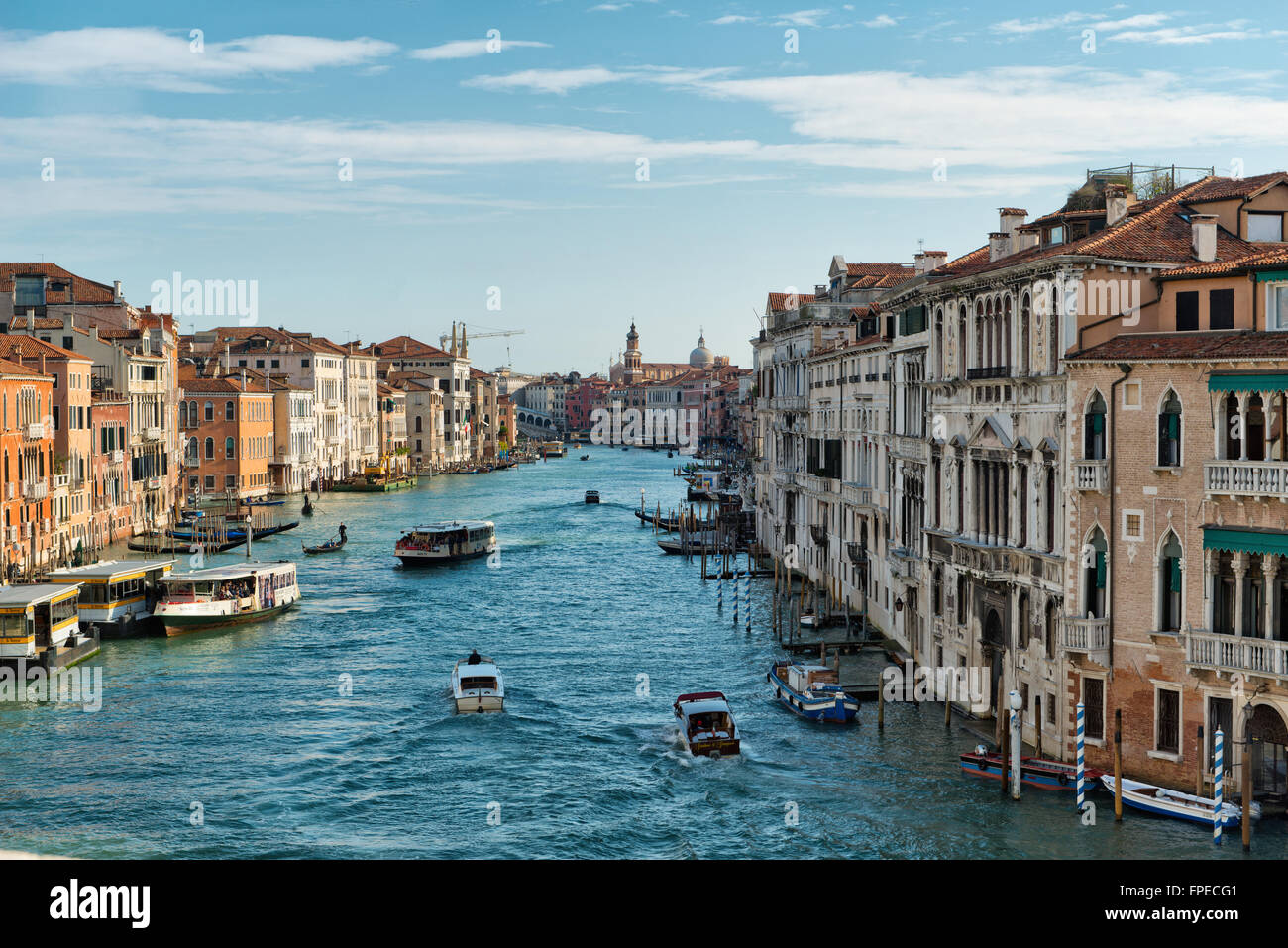 Boat traffic on the Grand Canal, Venice with a vaporetto and private boats plying the water between the historic - Stock Image