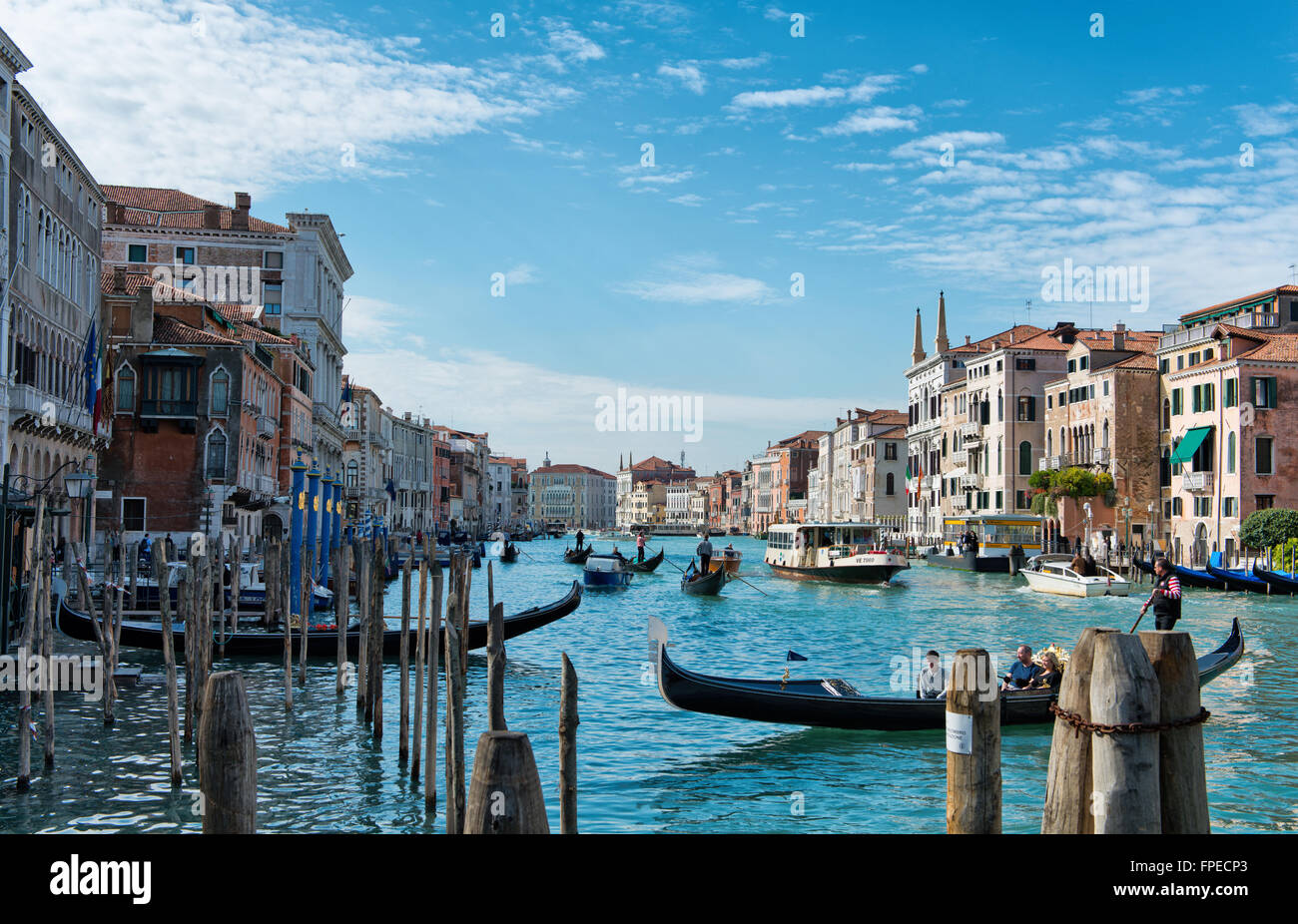 Boat traffic on the Grand Canal, Venice, with gondolas, private craft and a vaporetto or water bus passing old historical - Stock Image