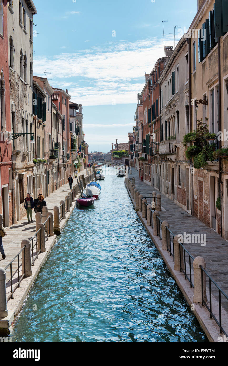 View of Canal and Pedestrians on Waterfront Promenades Through Residential Building Lined Street Scene in Venice, - Stock Image