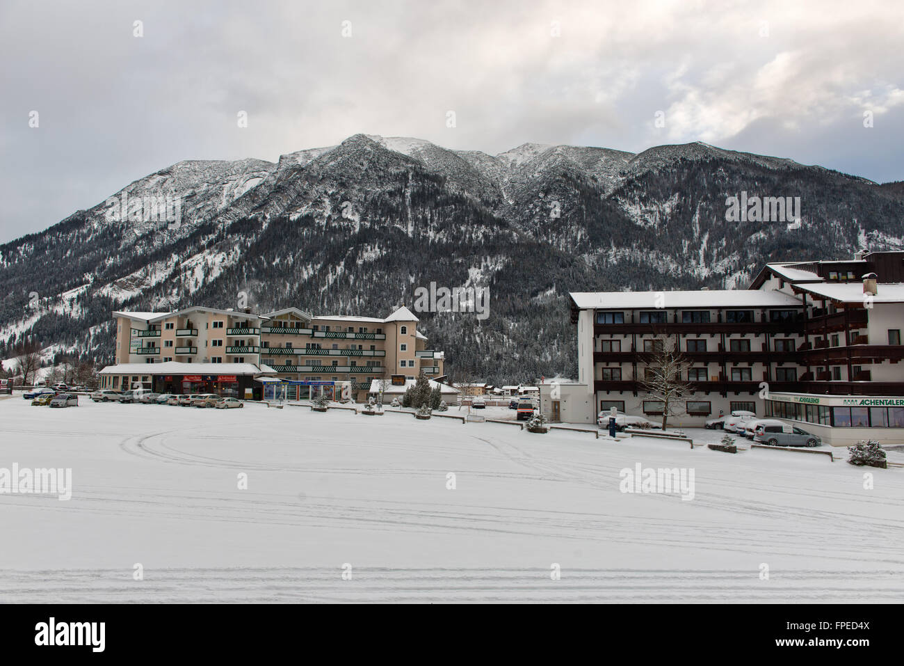 Village in Achenkirch, Austria with large mountain in background during cold, overcast winter day - Stock Image