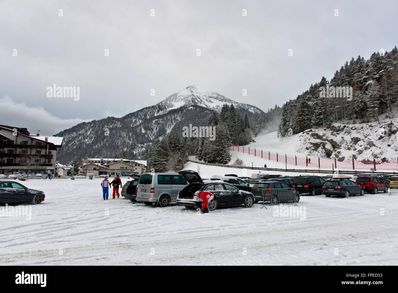 Ski resort village in Achenkirch, Austria with many parked cars near hill with hotel and large mountain in background - Stock Image