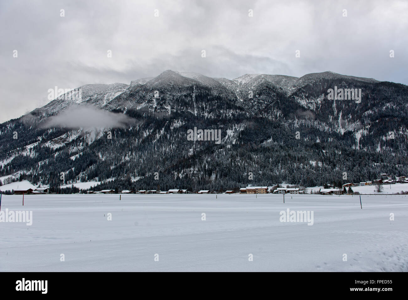 Cross country skiing resort in Achenkirch, Austria with beautiful large mountain in background under overcast sky - Stock Image