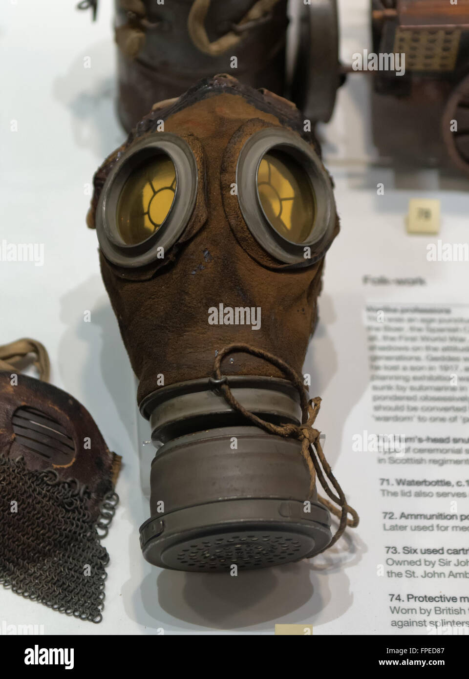Single poisonous gas mask for soldier with other objects on display in case at museum - Stock Image