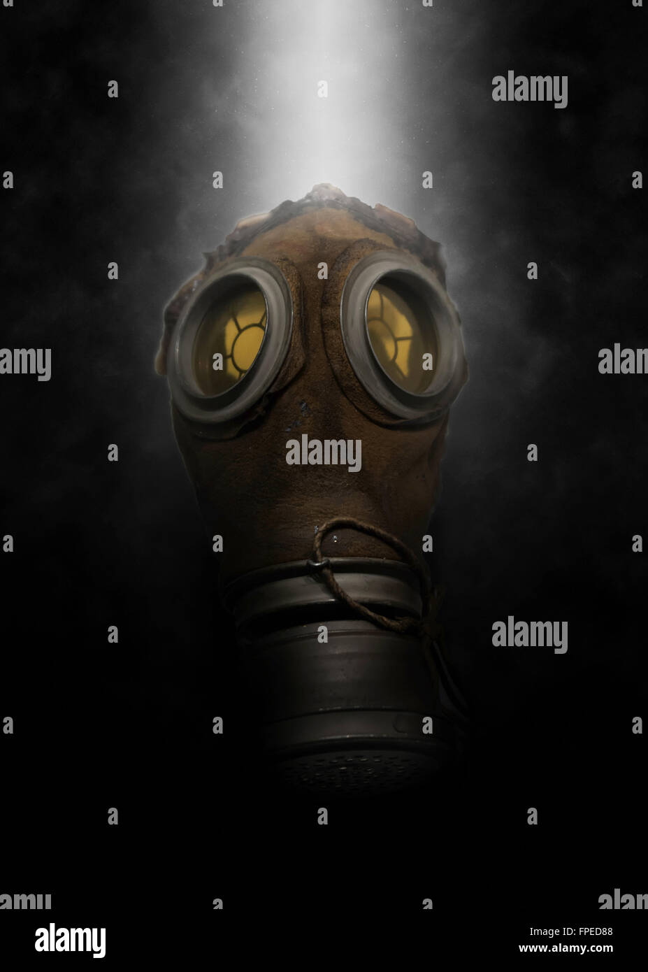 Single poisonous gas mask for soldier with with spray of mist behind it over dark gloomy background - Stock Image
