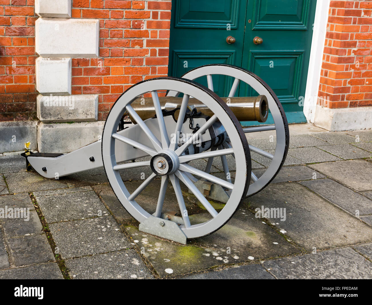 Single historic antique cannon on wheels locked to the ground outdoors as a display of warfare - Stock Image