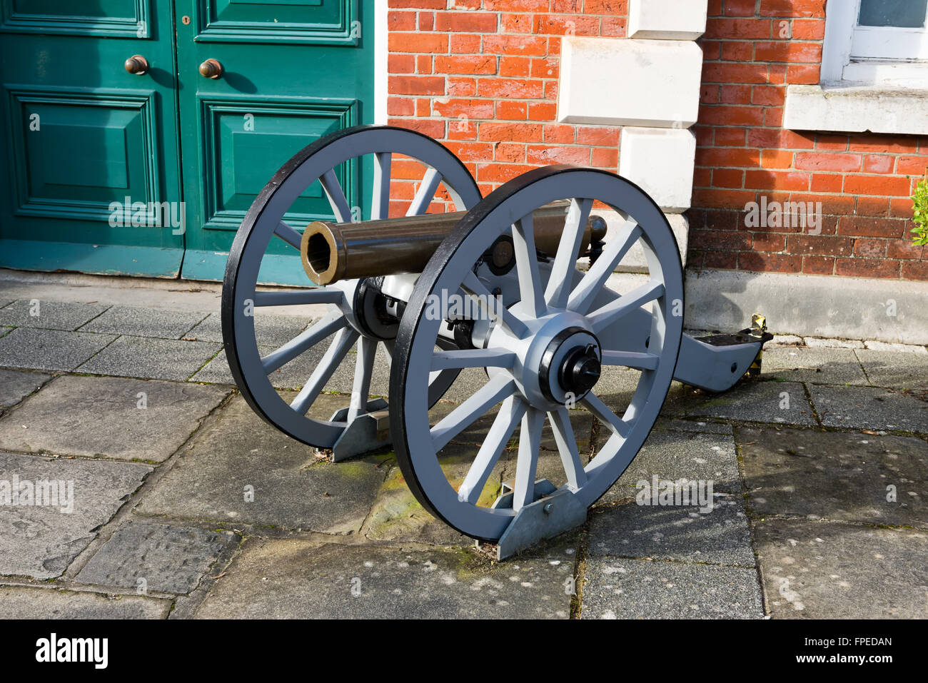 Historic antique cannon on wooden wheels locked to the ground outdoors as a display of warfare - Stock Image