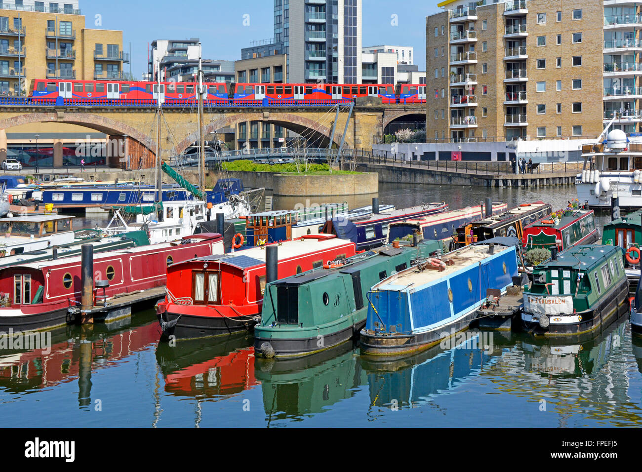 Assortment of narrowboats moored in Limehouse Basin with Docklands Light Railway train on brick viaduct East London - Stock Image
