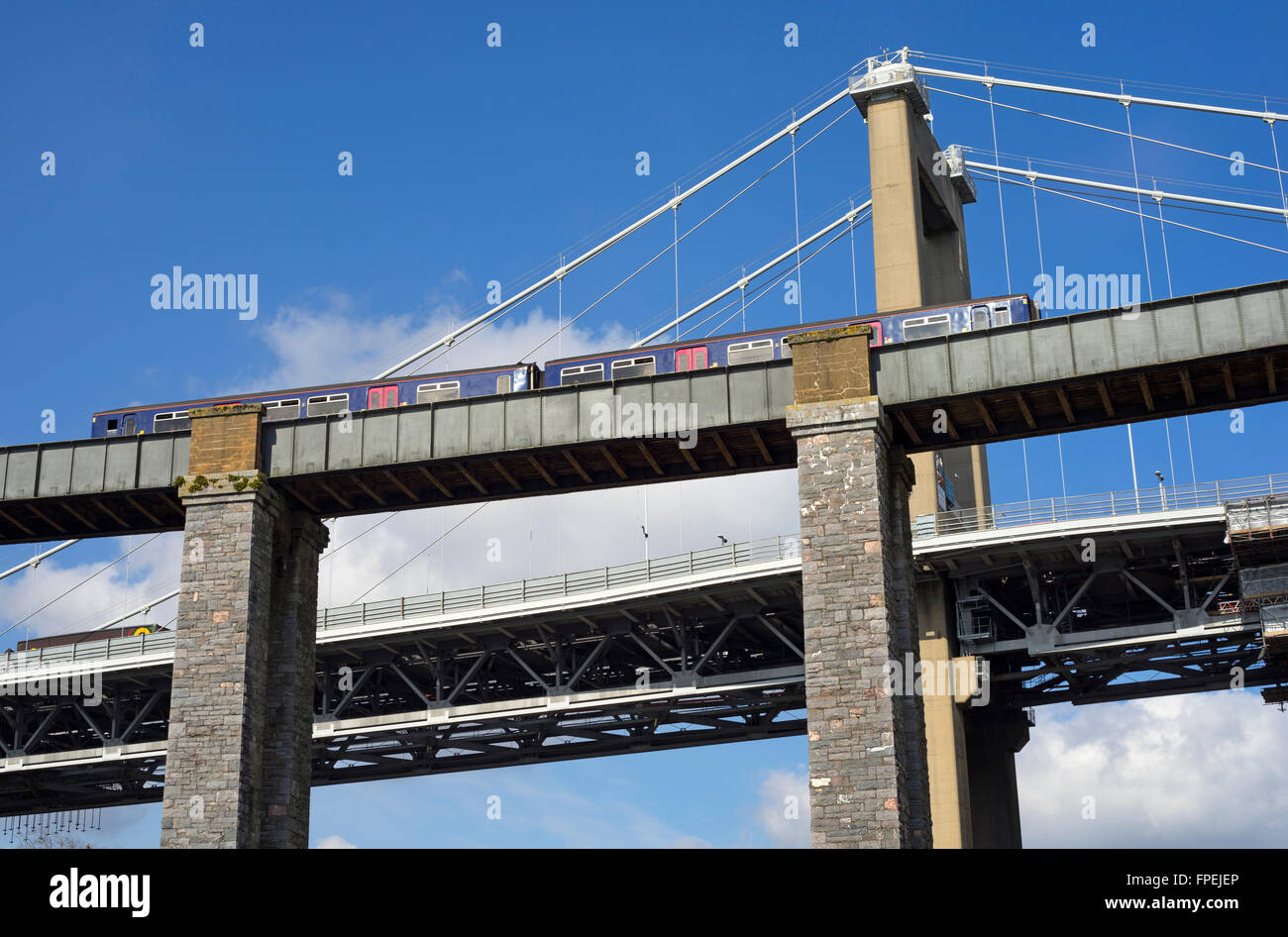 Train crossing the Royal Albert Bridge over the river Tamar above Saltash with the Tamar road bridge in the background. Stock Photo
