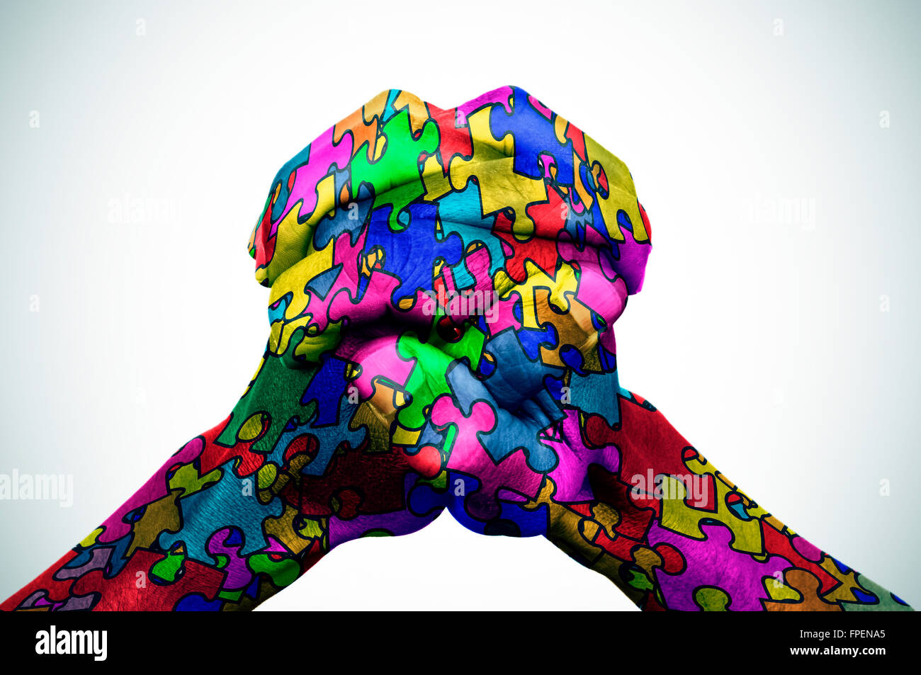 man hands put together patterned with many puzzle pieces of different colors, symbol of the autism awareness, with - Stock Image