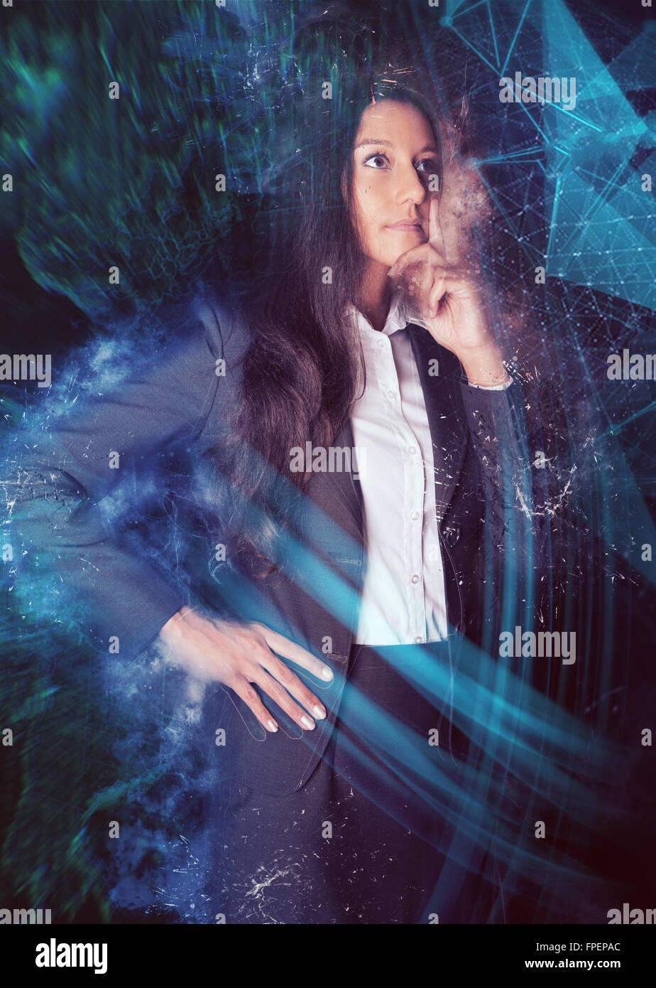 Three Quarter Length Portrait of Thoughtful Young Business woman Wearing Suit Standing with Hand on Chin in front Stock Photo