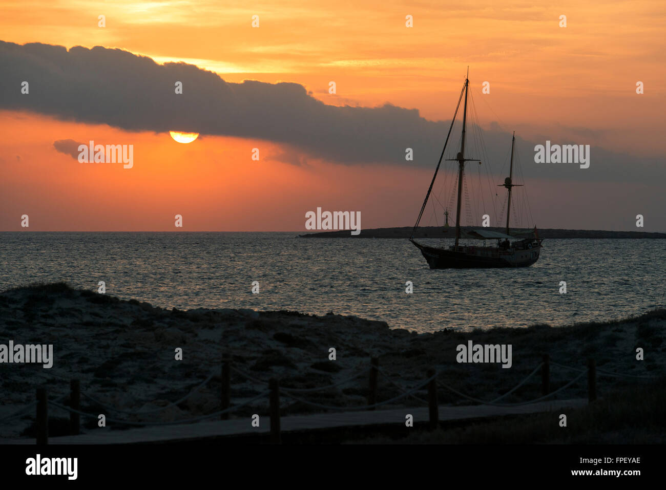 Ses Illetes Beach, Balearic Islands, Formentera, Spain. Boat and backlights in the sunset. - Stock Image