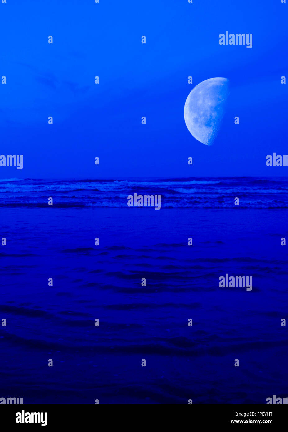 Moon over the blue ocean.The blue hour. - Stock Image