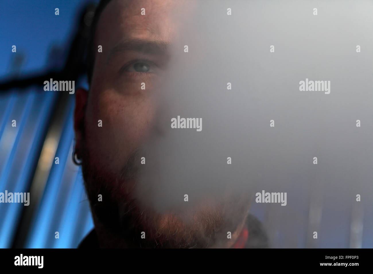 Man using electronic cigarette. - Stock Image
