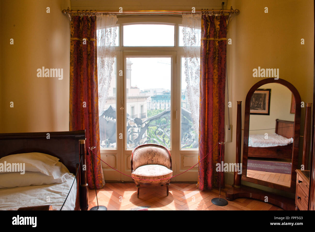 Interior of a restful vintage bedroom with comfortable bed, round chair, mirror and curtains at a window with city - Stock Image
