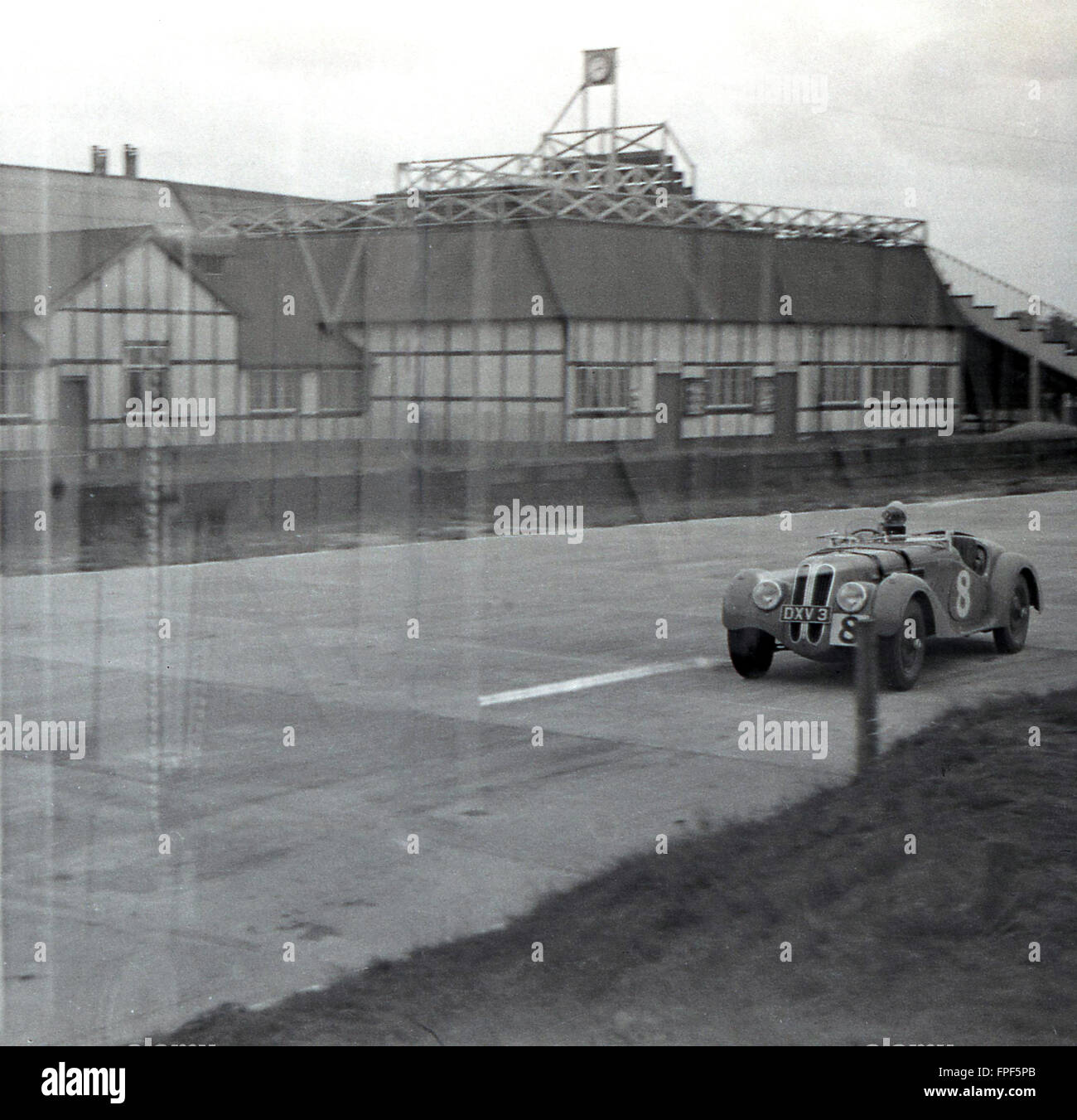1930s historical, motor racing car goes round Brooklands race track, Weybridge, Surrey. Opened in 1907, the circuit - Stock Image