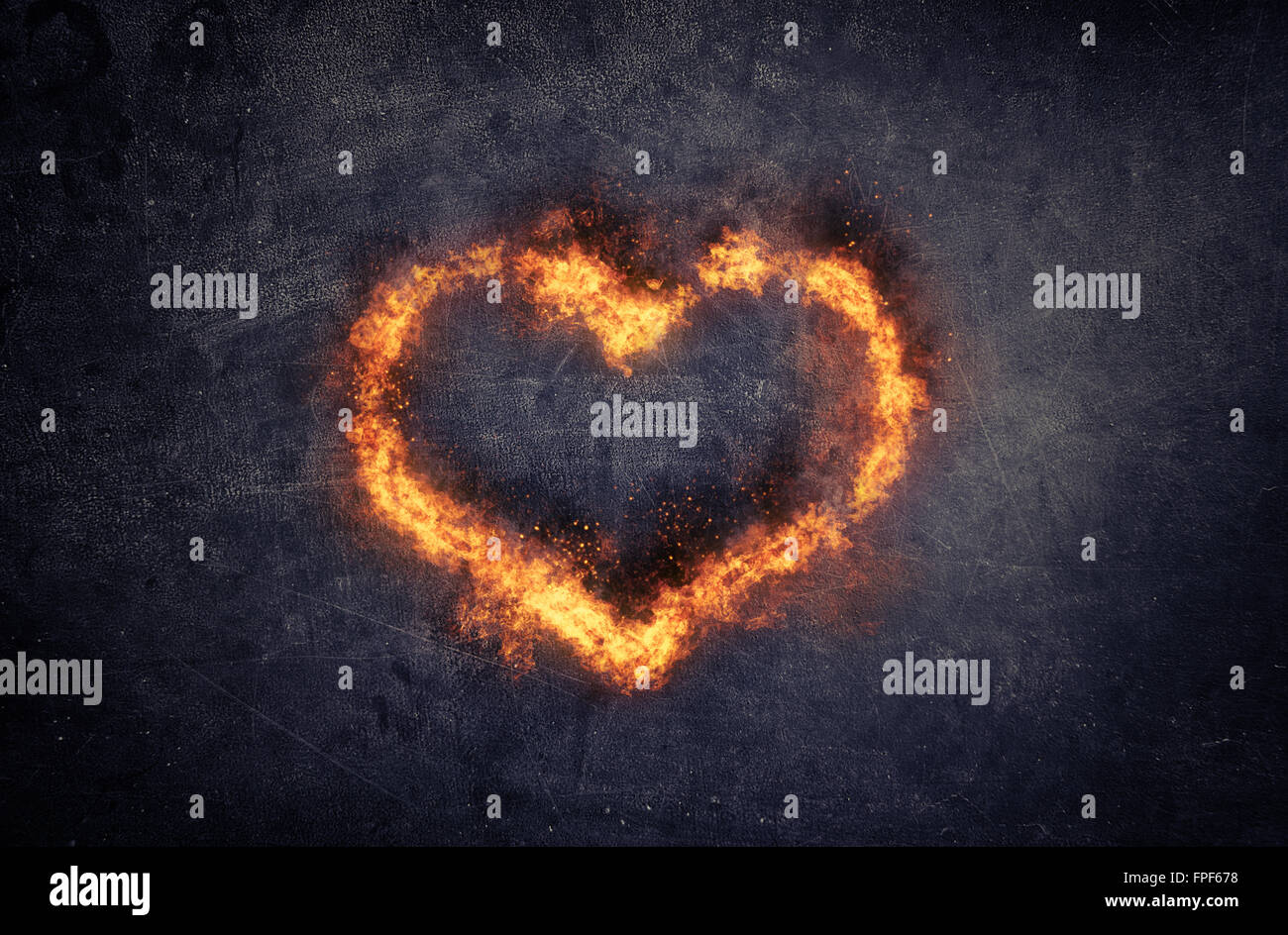Burning heart - heart-shaped ring of fire and orange flames over a textured dark background with copyspace conceptual - Stock Image