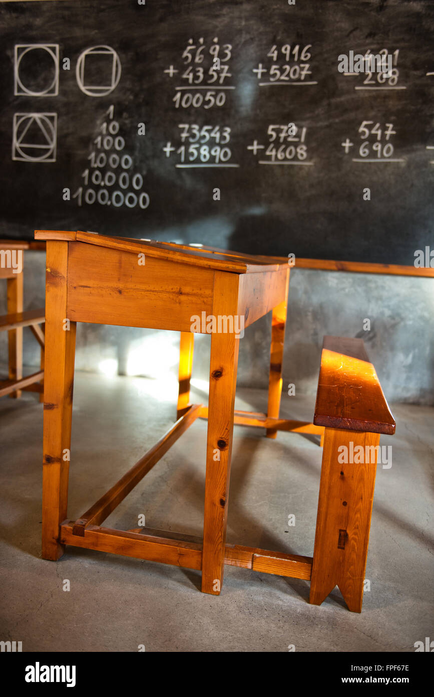 Old Fashioned Rustic School Room With Wooden Student Desks And Various  Mathematical Problems Written On The Blackboard Waiting To Be Solved