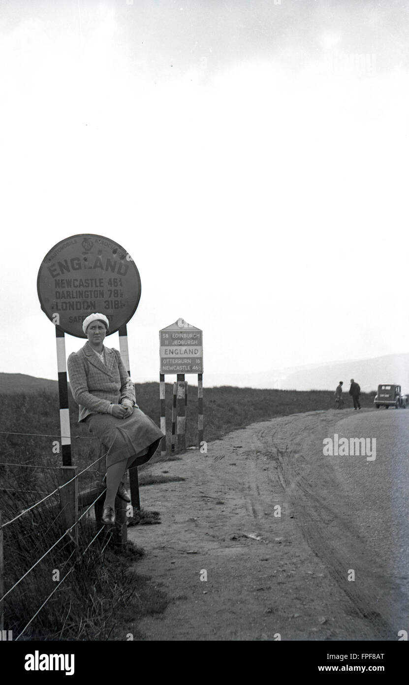 1930s historical, Lady sitting roadside on a fence in front of the AA sign for England - Newcastle, Darlington and - Stock Image