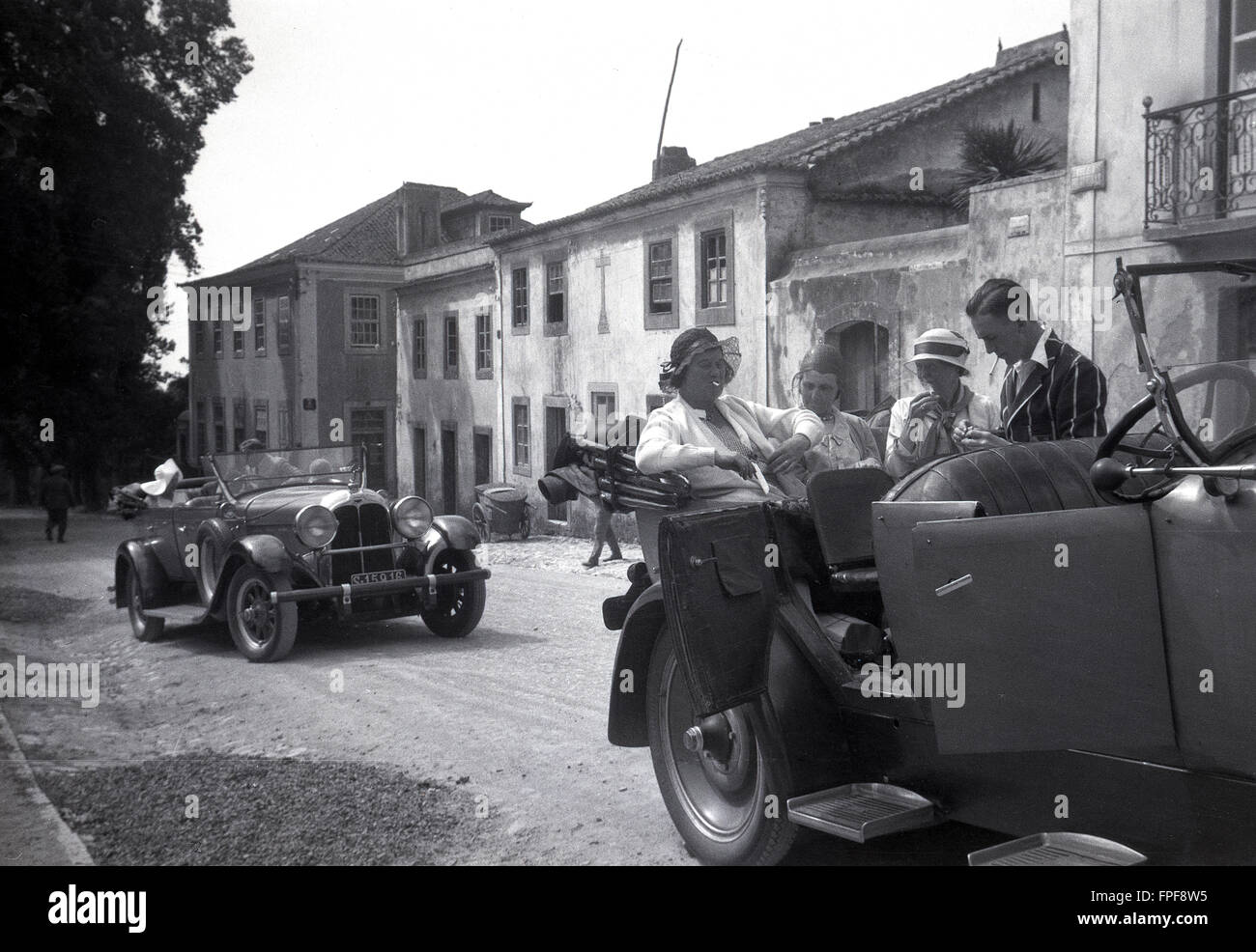 1930s historical, people on a Grand Tour of Europe in an open topped car enjoying a cigarette. - Stock Image