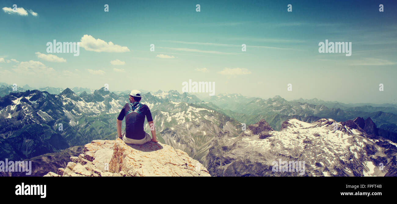 mountain climber sitting on the edge of a rock facing away from the