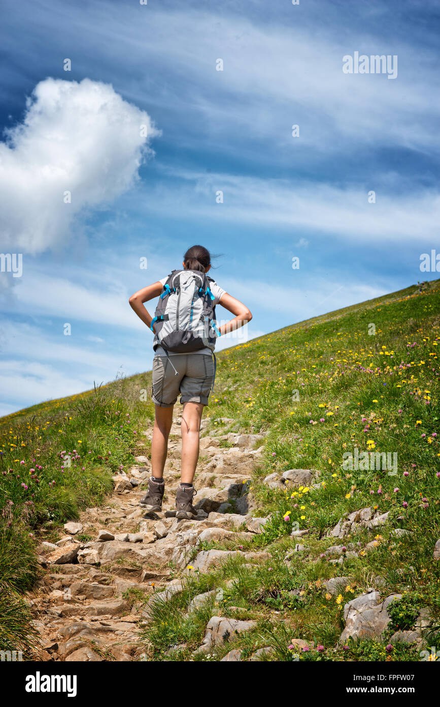 Rear View of Female Hiker Pausing for a Break on Rocky Mountain Trail, Low Angle View of Hiker Ascending Hillside - Stock Image