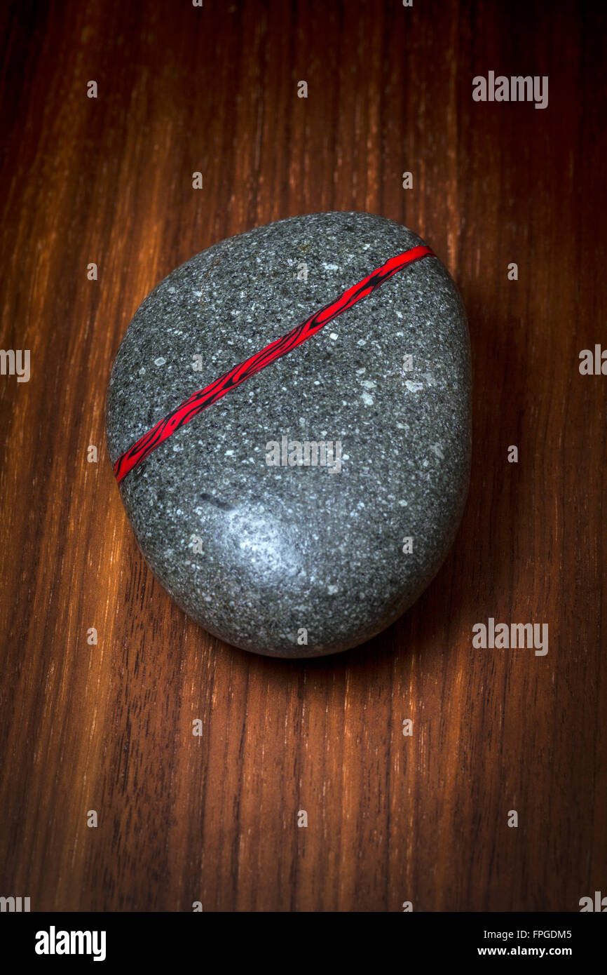 Natural pebble with an inlay of black and red resin vein. An original creation photographed in the studio on a walnut - Stock Image