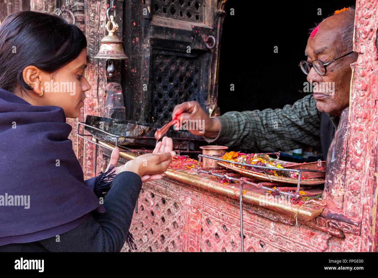 Nepal, Patan.  Female Worshiper Receiving Red Kumkuma (Sindoor) Powder at a Hindu Temple. - Stock Image