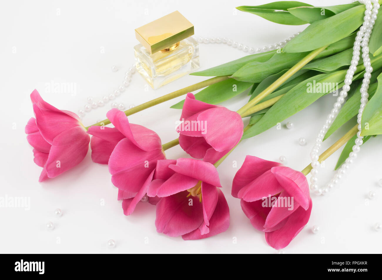 bouquet of red tulips, perfume and bead lying - Stock Image