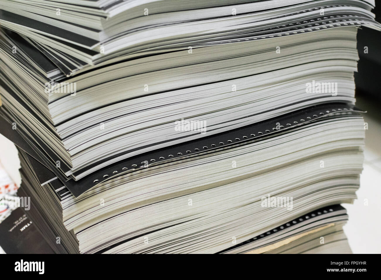 stack of black perforated printed sheets - Stock Image