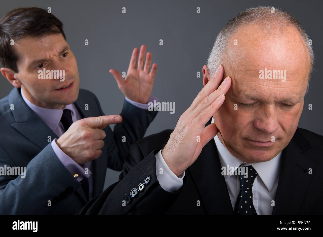 Businessman pointing his finger at a work colleague, who feels stressed. - Stock Image
