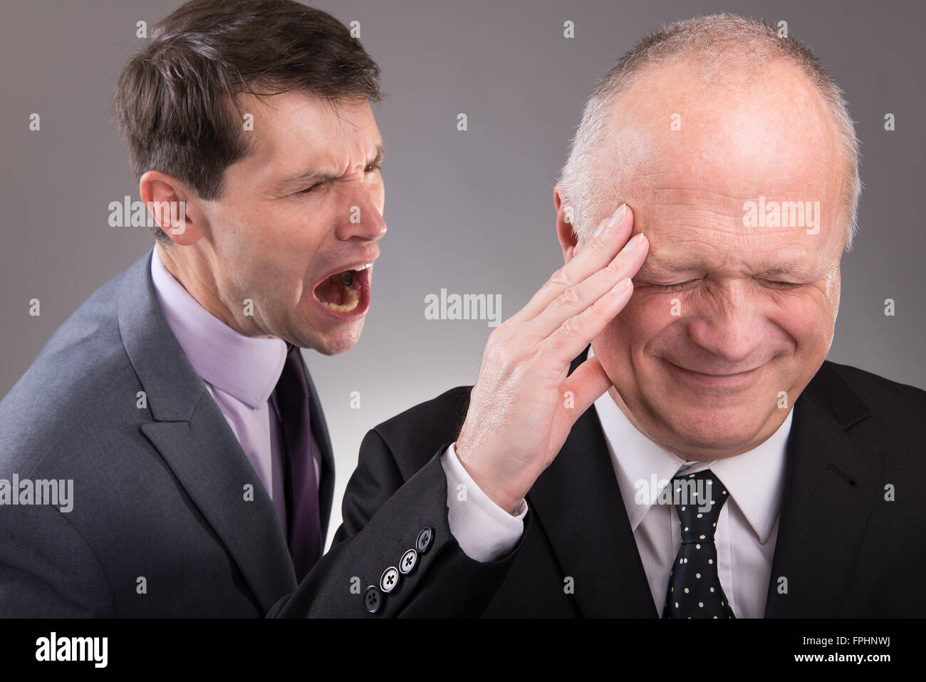 Stressed businessman in the foreground, with angry work colleague shouting at him from behind. - Stock Image
