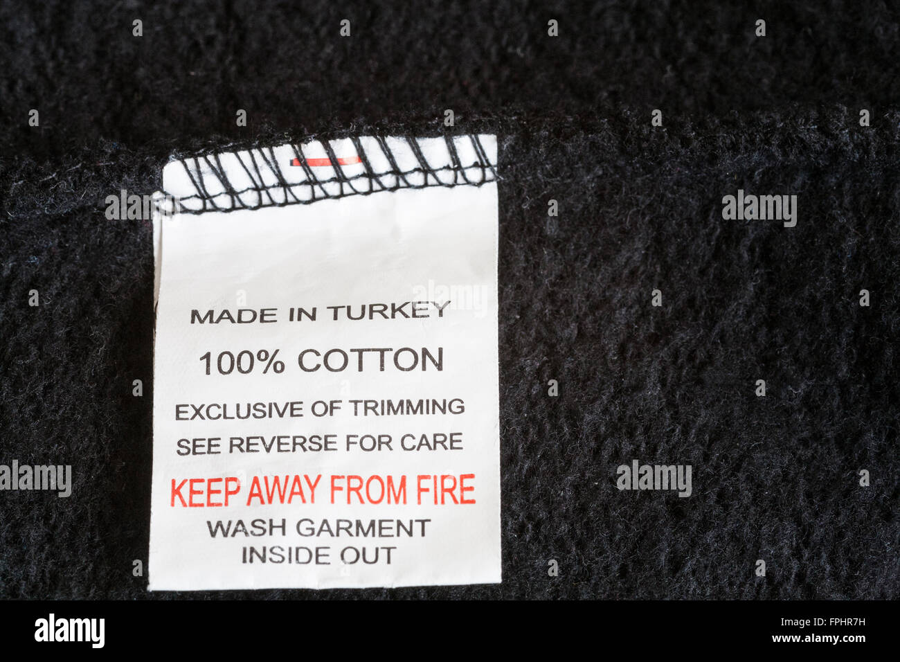 Close up label in black 100 % cotton fleece inflammable garment made in Turkey low cost manufactured product made - Stock Image