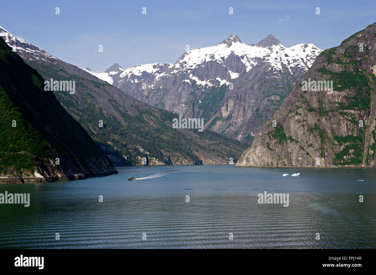 Small tour boat heads toward glacier as cruise boat heads out of Tracy Arm Fiord. - Stock Image