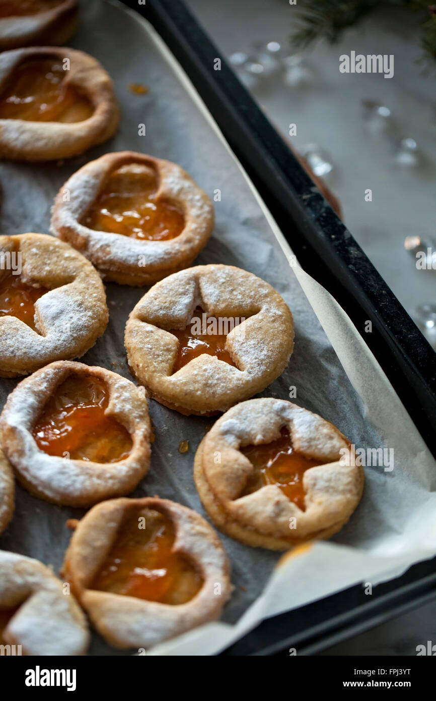 Linzer cookies with apricot jam dusted with powdered sugar on a baking tray - Stock Image