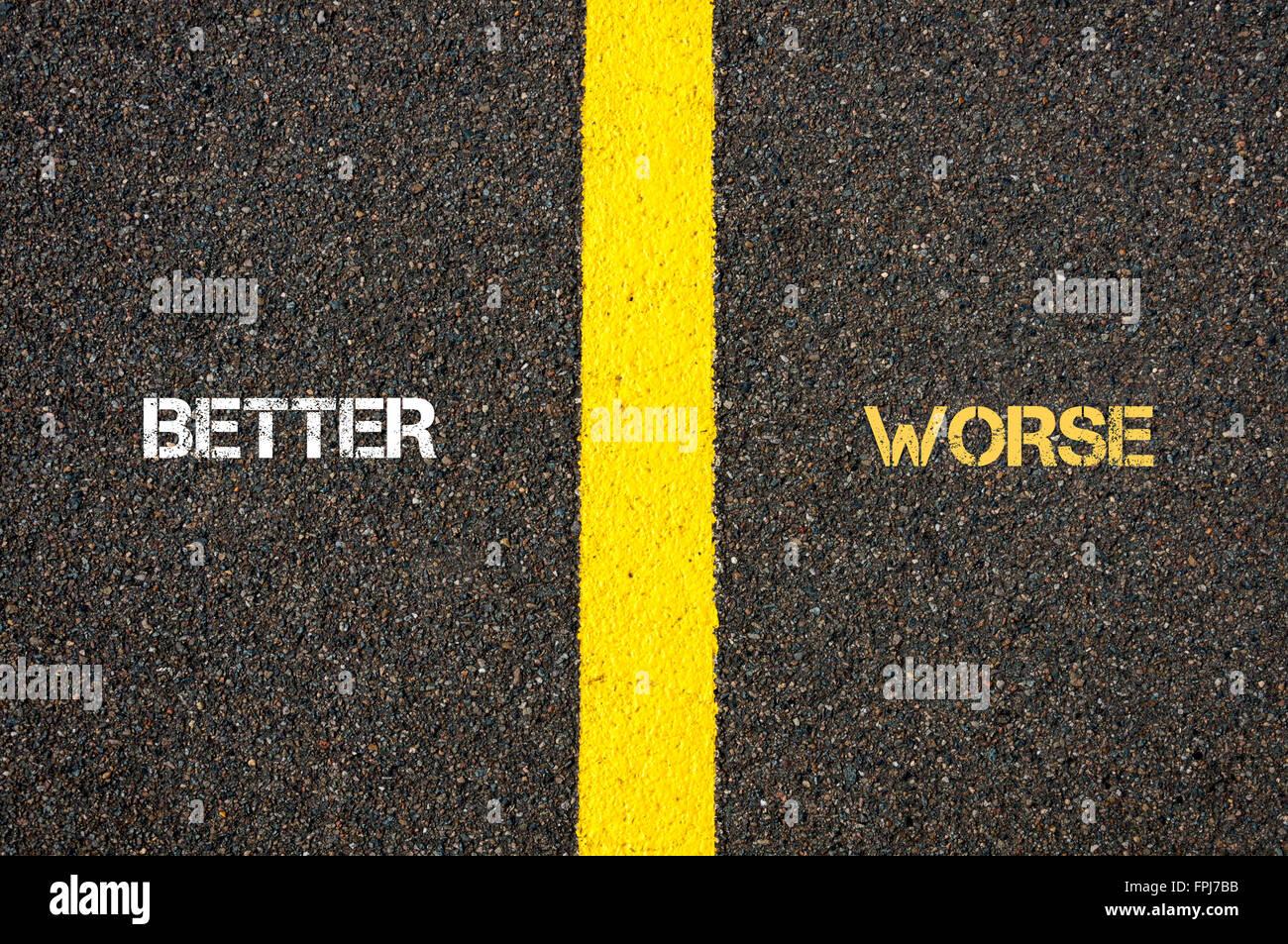 Antonym concept of BETTER versus WORSE written over tarmac, road marking yellow paint separating line between words Stock Photo