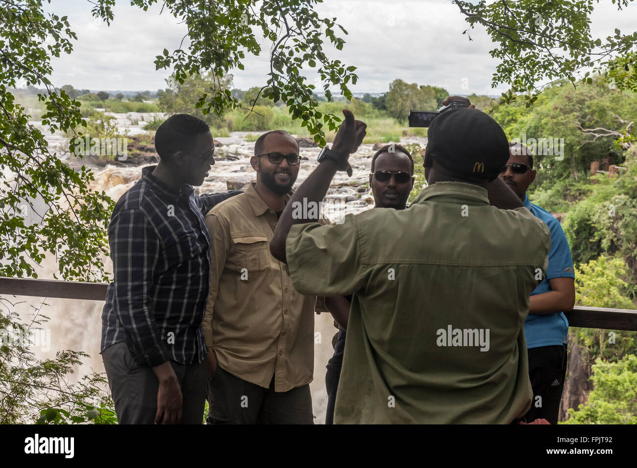 African tourists having their photograph taken at Mosi-oa-tunya National Park, (Victoria Falls), Livingstone, Zambia, - Stock Image