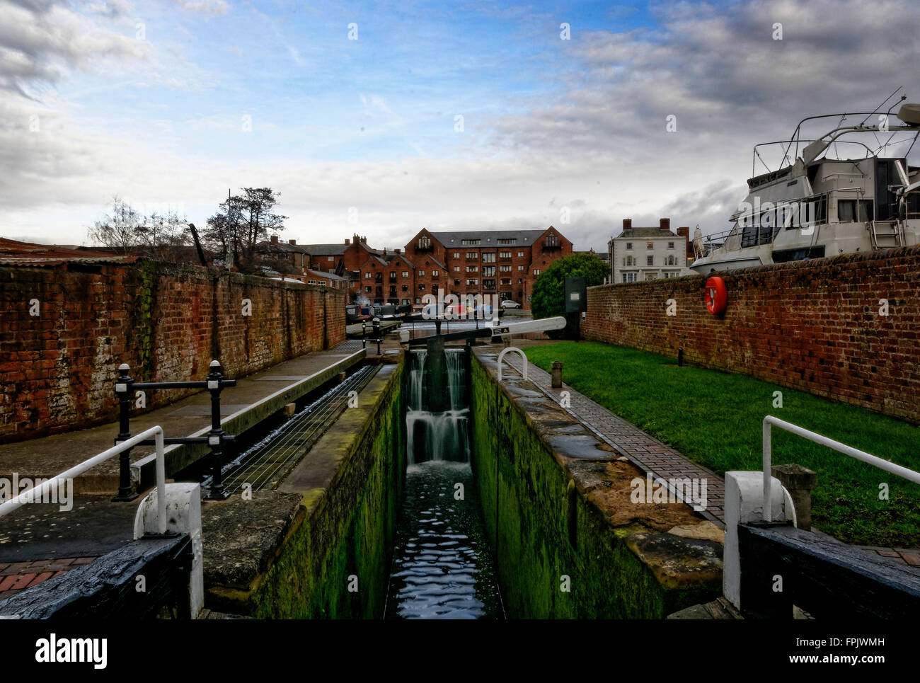 Water cascades through a half open lock gate linking the River Severn at the Canal basin at Stourport upon Severn - Stock Image