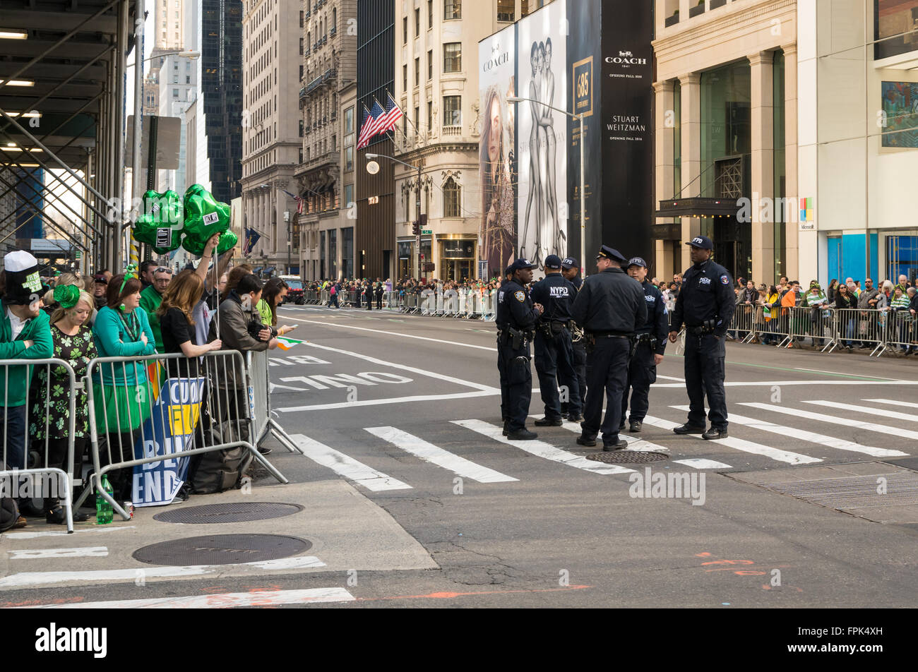 Police talking before the start of the annual St. Patrick's Day parade in New York City, with spectators looking - Stock Image