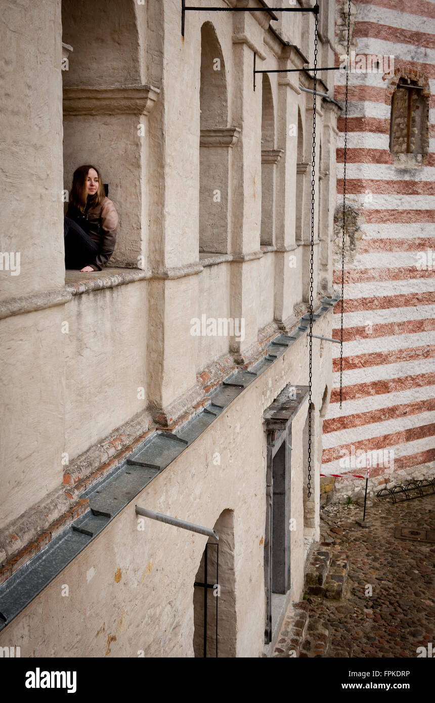 Wistful woman in castle window, adult girl with thoughtful face sightseeing historic building ruins with reflective - Stock Image