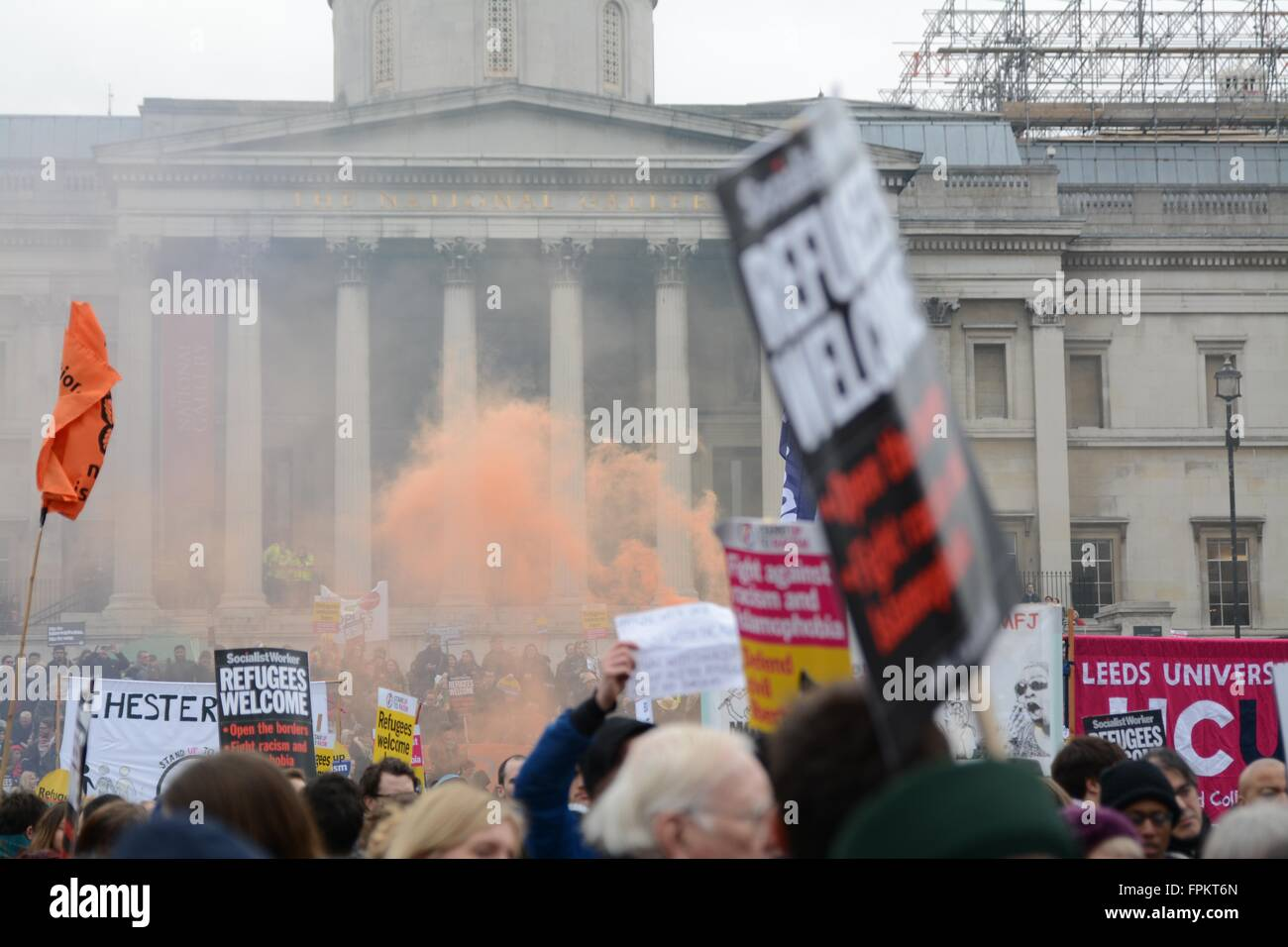 London, UK. March 19th 2016. Colour smoke rises from Trafalgar Square as thousands rally against racism in London. - Stock Image