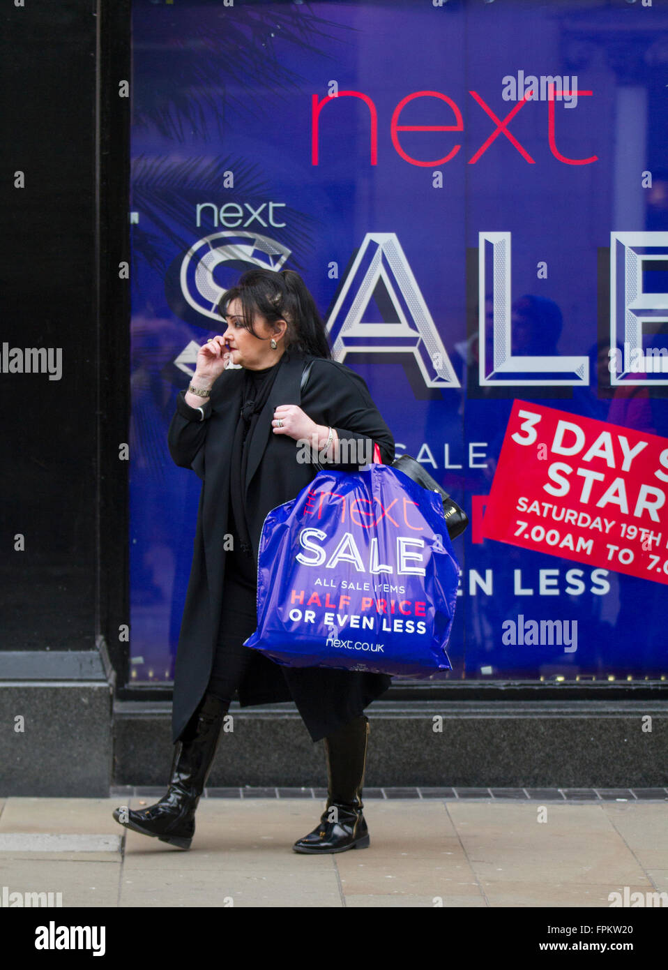 Woman carrying goods, in a shopping bag,  purchased from Next clothing shop Half Price Sale Event in Chester, Cheshire, - Stock Image