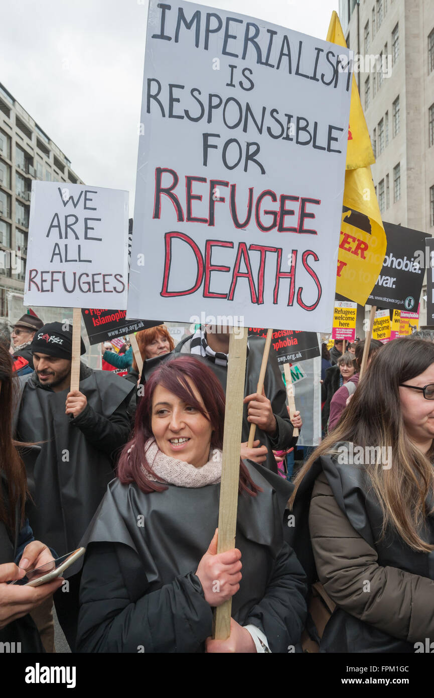 London, UK. Saturday 19th March 2016. A woman holds a placard 'Imperialism is Responsible for Refugee Deaths' - Stock Image