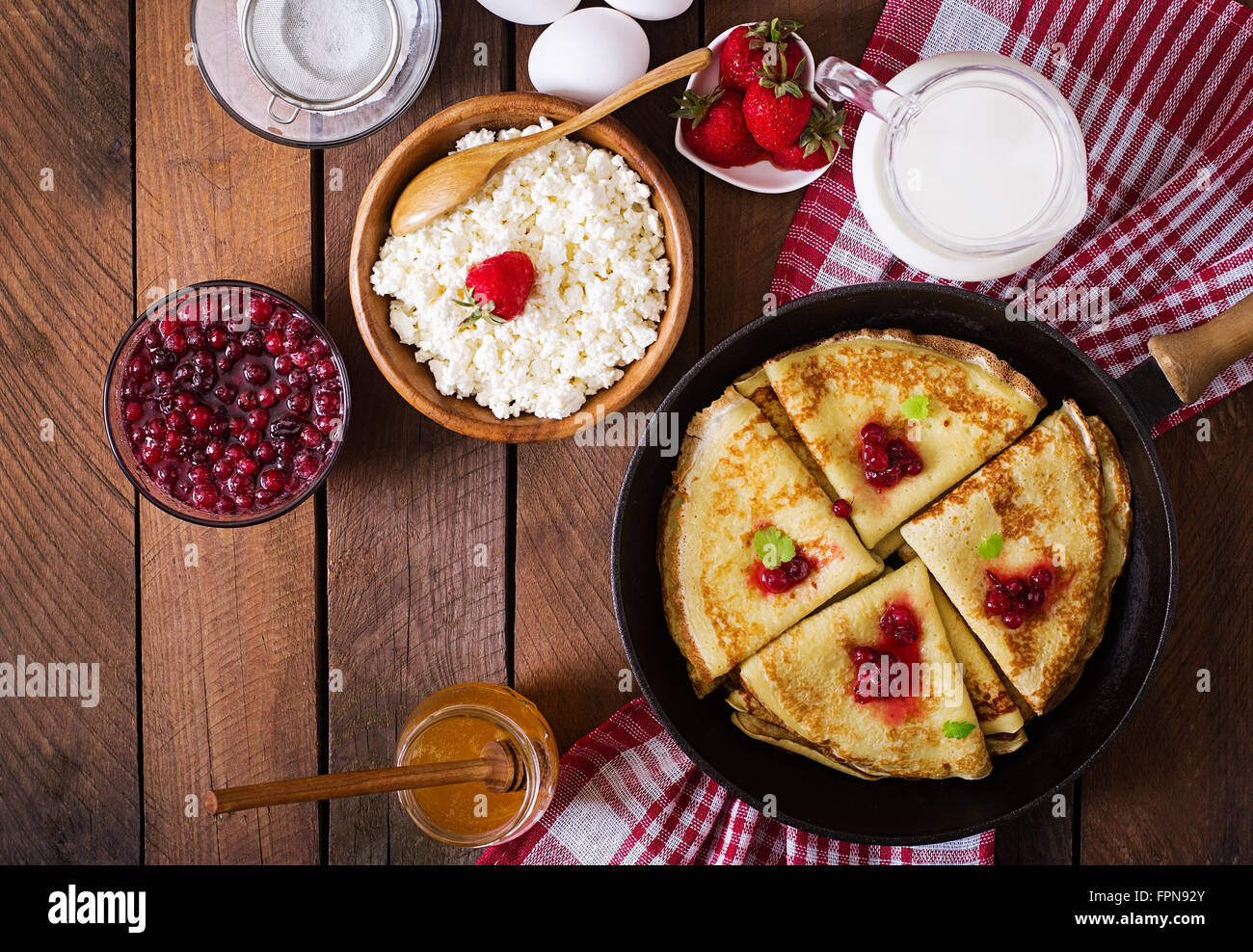 Golden pancakes with cranberry jam and honey in a rustic style. Top view - Stock Image